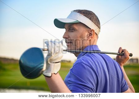 Weighing up his next shot. Mature male golfer thinking about his next shot, holding his golf club over his shoulders