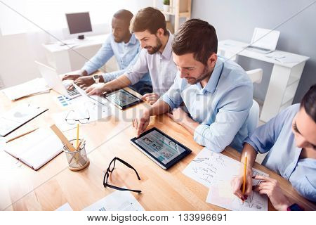Set goals. Positive concentrated colleagues sitting at the table while working in the office