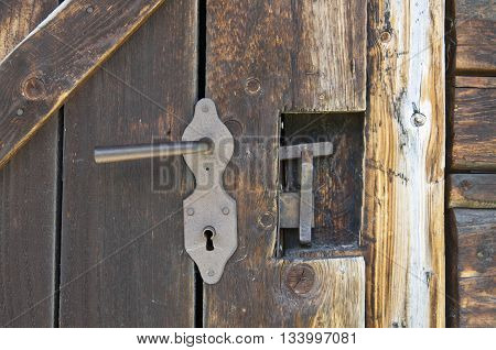 Old brown wooden outhouse door lock details