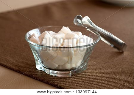 Sugar bowl filled with sugar cubes and tongs