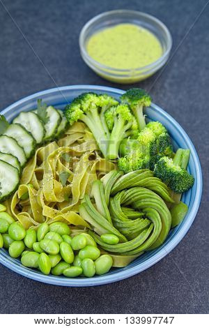 Spinach pasta with cucumber, broccoli, avocado and edamame