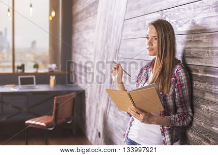 Thoughtful young woman holding notepad and pencil in interior with wooden wall chair and desk