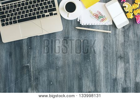 Top view of dark wooden office desktop with laptop keyboard coffee cup white smartphone and various stationery items. Mock up