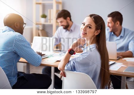 Full of joy. Positive charming smiling woman sitting at the table and looking at you while her colleagues working I the background