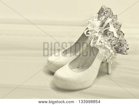 Wedding theme soft background: the bride's shoes and garter blurred in sepia filter.