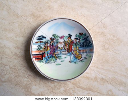 Chinese porcelain plate. At the plate depicts a scene from the life of the ancient Chinese.