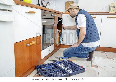 Worker repairing the sink in the kitchen. Man looks at the sink and holding a wrench. Next to the man lies toolbox.