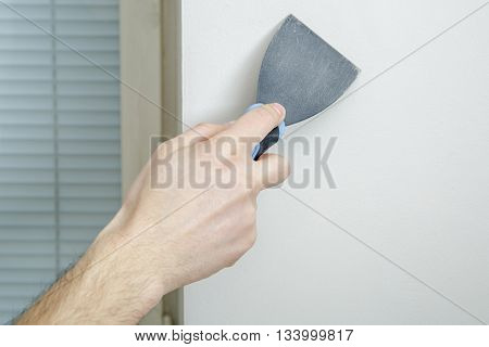 Male hand holds putty knife on the wall near the corner. Finishing work.