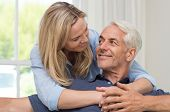 Portrait of a loving mature senior woman embracing man from behind at home. Happy senior couple rela poster