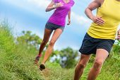 Fitness athletes trail running - athletic legs closeup lower body crop of man and woman working out. poster