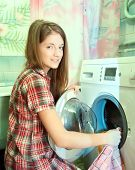 stock photo of washing machine  - Teenager girl doing laundry at her home - JPG