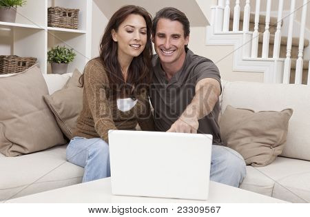 Attractive, successful and happy middle aged man and woman couple in their thirties, sitting together on sofa at home using a laptop computer.