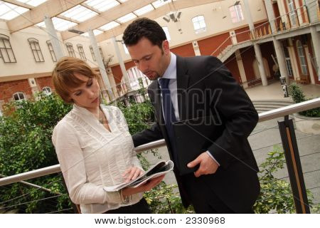 Business Man And Woman Reading News In Magazine