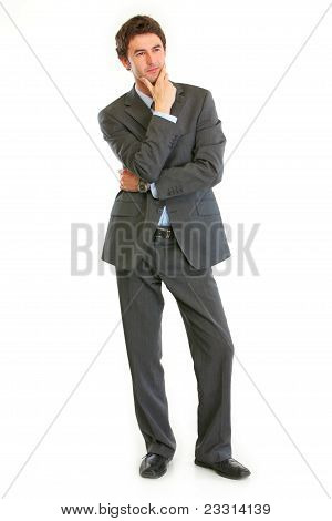 Full Length Portrait Of Pensive Businessman With Hand Near Face
