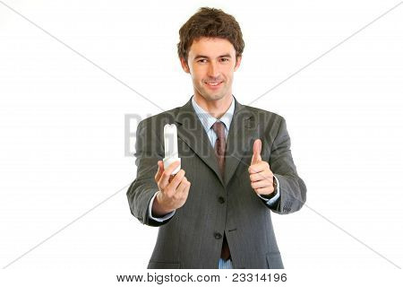 Modern Businessman With Fluorescent Lamp Showing Thumbs Up Gesture. Environmental Protection Concept