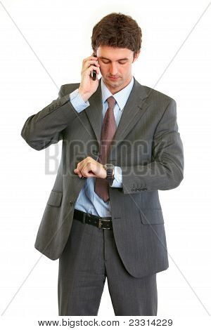 Modern Businessman Talking On Phone And Looking On Watch
