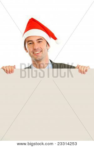 Smiling Guy In Santa Hat Holding Blank Billboard