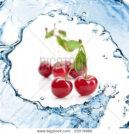 Red cherry with leaves and water splash isolated on white