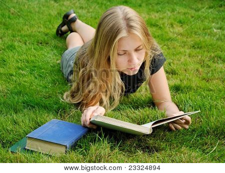 Girl With Book On Grass