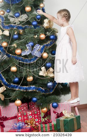Christmas time - little girl decorating a Christmas tree