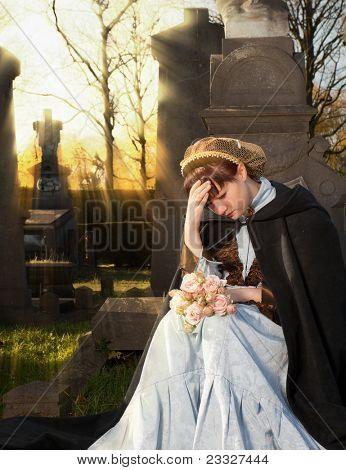Viuda joven victoriano llorando sobre una lápida en Halloween