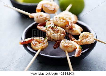 skewers with grilled prawns and lime wedges