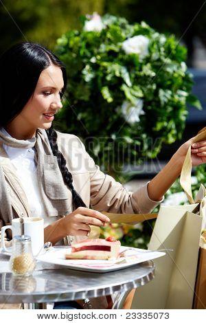 Imagem de uma mulher feliz no café ao ar livre, olhando para paperbags em ambiente urbano