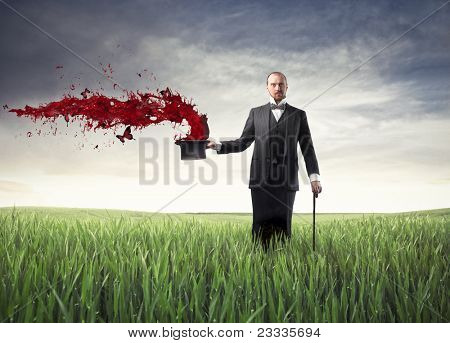 Magician on a green meadow with red paint coming out of his cylinder hat