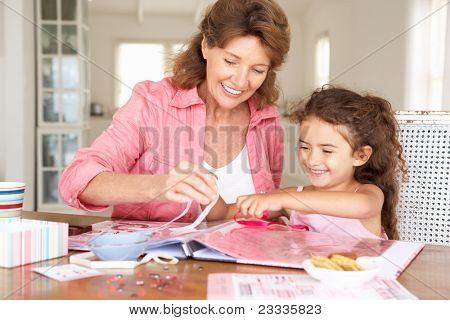 Senior woman scrapbooking with granddaughter