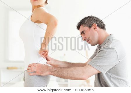 Chiropractor examining a woman's back in a room
