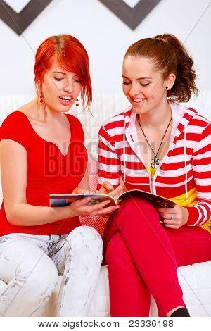 Cheerful Girlfriends Sitting On Sofa And Looking Fashion Magazine