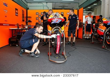 SEPANG, MALAYSIA - FEBRUARY 22: Mechanics from the Repsol Honda Team work on Casey Stoner's bike at the 2011 MotoGP winter tests at the Sepang International Circuit. February 22, 2011 in Malaysia.