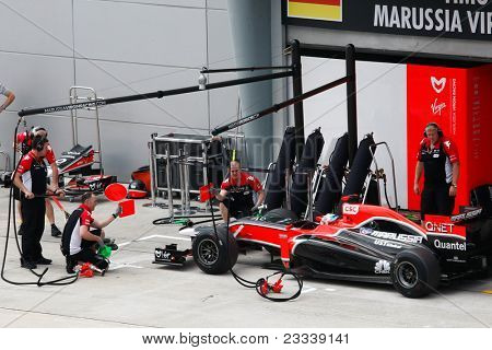 SEPANG, MALAYSIA - APRIL 8: Marussia Virgin Racing team crew checks on Timo Glock's car on the first practice day of the Petronas Malaysian F1 Grand Prix on April 8, 2011 Sepang, Malaysia.
