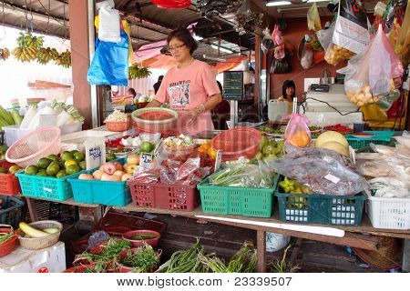 KUCHING - MAY 13: An unidentified lady packs the vegetables at her shop in town, May 13, 2011 in Kuching, Borneo Island. Most of the shops cater to the town-folks and a growing number of tourists.