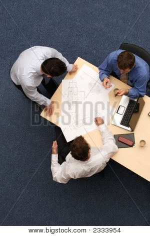 Innovation - Three Business People Working Over Plans