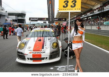 SEPANG - JUNE 19: Hankook KTR's race queen carries placard in front of the team's Porsche 911 car at the start of the Japan SUPER GT Round 3 race on June 19, 2011 in Sepang, Malaysia.
