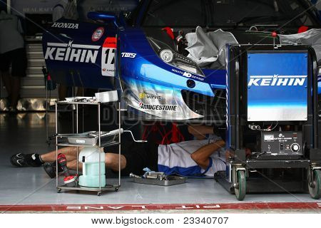 SEPANG - JUNE 18: The mechanics of Keihin Real Racing working on the Honda HSV-010 car in the garage in the Sepang International Circuit at the SUPER GT Round 3 on June 18, 2011 in Sepang, Malaysia.