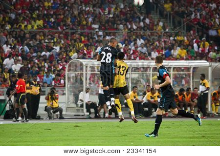 BUKIT JALIL, MALAYSIA - JULY 13: Arsenal's Kieran Gibbs (28) heads away the ball against Malaysia on July 13, 2011 in Stadium Bukit Jalil, Malaysia. English league team Arsenal is on an Asia Tour.