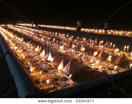 PUCHONG, MALAYSIA - AUGUST 27: Prayer offerings for the ancestors, consisting of joss-sticks, candles and food line the grounds at the 'hungry ghost festival' in Puchong, Malaysia on August 27, 2011.
