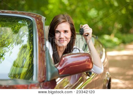 Joyful Teenager Female Driver Holding Car Key Arm Out in Convertible