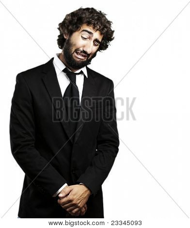 portrait of young business man with suit crying against a white background