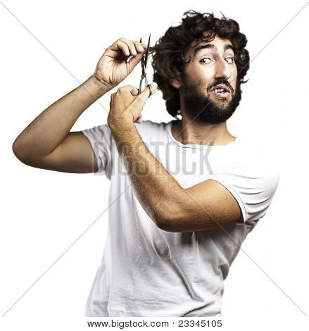 portrait of young man cutting the hair against a white background