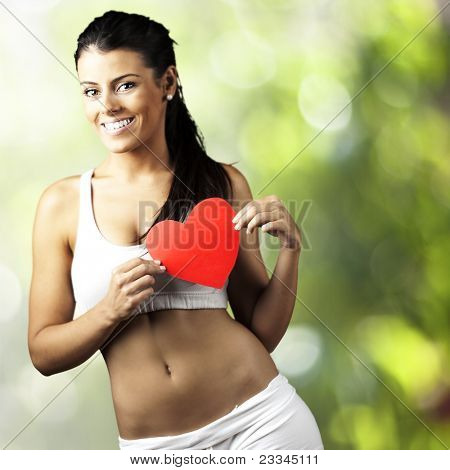 portrait of healthy young woman with red heart symbol at park