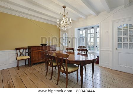 Dining room with white ceiling wood beams and gold walls