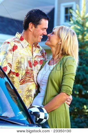 Happy smiling couple near convertible car. People outdoors.