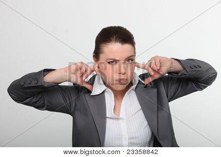 Trabalhador de escritório morena com os dedos nos ouvidos