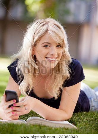 Portrait of an attractive university student sending a text message on a cell phone