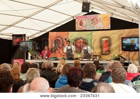 LUDLOW, UK-SEPTEMBER 11: Ludlow Food Festival, an audience watches chef Jason Hodnett, with his assistants give a cookery demonstration in the grounds of Ludlow castle on September 11, 2011