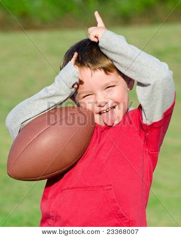 Young boy with football celebrating or trash talking after scoring
