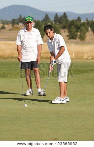 Teen Golfer Putts The Ball.